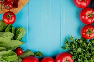 top view of vegetables as spinach tomato coriander with knife on cutting board on blue background with copy space