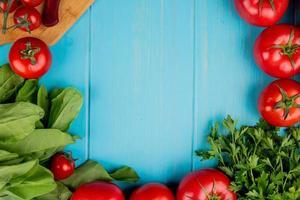Vista superior de verduras como espinacas, tomate, cilantro con cuchillo en la tabla de cortar sobre fondo azul con espacio de copia