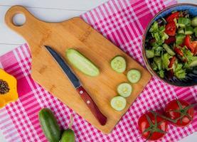 Vista superior del pepino cortado y en rodajas con un cuchillo en la tabla de cortar y ensalada de verduras tomate pimienta negra sobre tela escocesa y fondo de madera