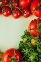 Vista superior de verduras como cilantro y tomate sobre fondo blanco. foto