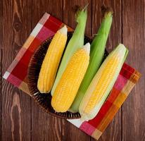 top view of cooked and uncooked corns in basket on cloth and wooden background photo