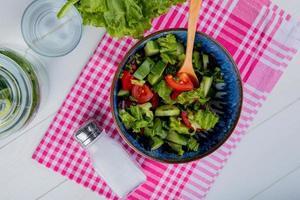 Vista superior de ensalada de verduras y sal sobre tela escocesa con agua de desintoxicación y lechuga sobre fondo de madera foto