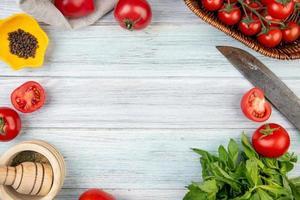 Vista superior de verduras como tomate hojas de menta verde con pimienta negra trituradora de ajo y cuchillo sobre fondo de madera con espacio de copia