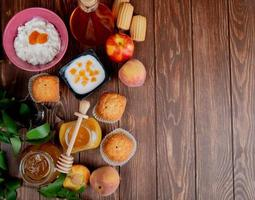 top view of jars of jams as peach and plum with cupcakes peaches cottage cheese on wooden background decorated with leaves with copy space