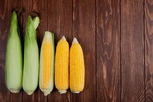 Vista superior de mazorcas de maíz cocidas y crudas en el lado izquierdo y fondo de madera con espacio de copia