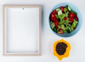 Ttop view of vegetable salad in bowl and black pepper seeds in bowl with frame on white background with copy space