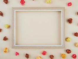 Top view of white frame with skittles popcorn around on white background with copy space