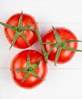 Vista superior de tres tomates sobre fondo de madera foto