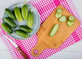 Vista superior de pepinos cortados y en rodajas sobre una tabla de cortar con los enteros en el plato y el cuchillo sobre un paño a cuadros y fondo de madera