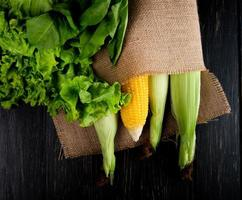 top view of cooked and uncooked corns in sack with lettuce and spinach on black background