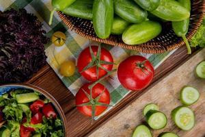 Vista superior de verduras como tomate pepino albahaca con ensalada de verduras sobre fondo de madera foto