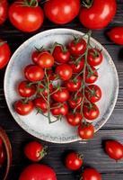 Vista superior de tomates en placa y otros sobre fondo de madera foto