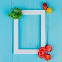 Vista superior de verduras como cilantro y tomates con marco blanco sobre fondo azul con espacio de copia