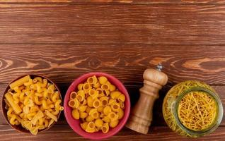 top view of different types of macaronis in bowls and salt on wooden background with copy space