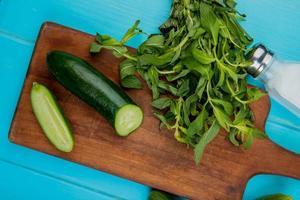 Vista superior de verduras como pepino cortado y menta en la tabla de cortar con sal sobre fondo azul. foto