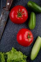 Vista superior de verduras como lechuga tomate pepino con cuchillo en la tabla de cortar como fondo