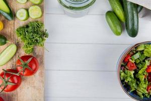 top view of vegetables as cucumber tomato coriander on cutting board and cucumbers in sack with vegetable salad on wooden background with copy space