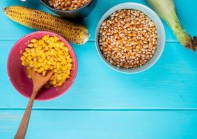 top view of bowls full of cooked and dried corn seeds with corn cobs on blue background