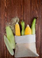 Top view of sack full of corns with corn shell and silk on wooden background