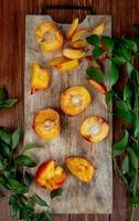 top view of cut and sliced peaches on cutting board on wooden background decorated with leaves with copy space