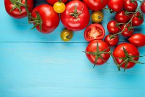 Top view of tomatoes on blue background with copy space