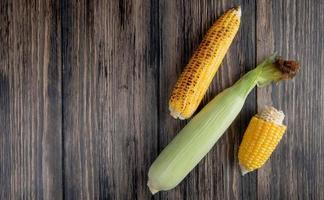 top view of cooked and uncooked corns on right side and wooden background with copy space photo