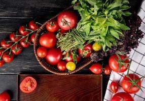 Vista superior de verduras como tomate hojas de menta verde albahaca en canasta y tomate cortado en bandeja sobre fondo de madera foto