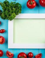 Vista superior de verduras como tomate y cilantro alrededor de la placa sobre fondo azul con espacio de copia