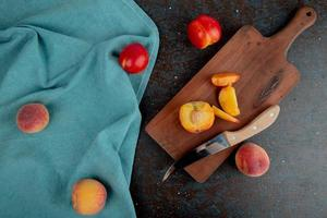 Top view of sliced peach with knife on cutting board with whole peaches on cloth on brown and black background