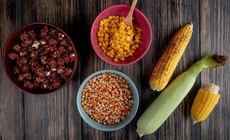 top view of bowls full of chocolate popcorn with cooked and dried corn seeds and corns on wooden background