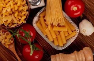 top view of ziti pasta in bowl with spaghetti and other types in bowl and spoon salt tomato garlic on wooden background