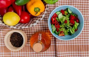 Top view of vegetable salad with lemon cucumber tomato pepper in basket with black pepper seeds and melted butter on plaid cloth background