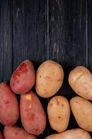 Top view of white and red potatoes on wooden background with copy space photo