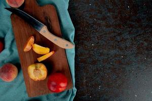 Top view of sliced peach with knife on cutting board with whole peaches on cloth on brown and black background with copy space photo