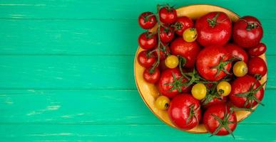 Top view of tomatoes in a bowl on a green background with copy space