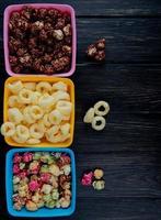 Vista superior de tazones de palomitas de maíz como bolos y chocolate con cereal pop de maíz sobre fondo de madera negra