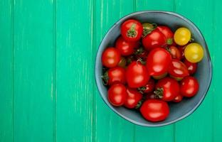 Top view of tomatoes in bowl on right side and green background with copy space
