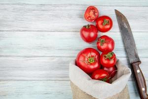 Top view of tomatoes spilling out of sack and knife on wooden background with copy space photo