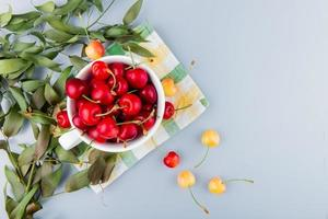 top view of cup full of red cherries on left side and white background decorated with leaves with copy space photo