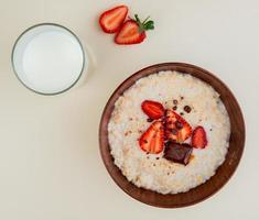 top view of bowl of oatmeal with cottage cheese chocolate and strawberries with glass of milk on white background