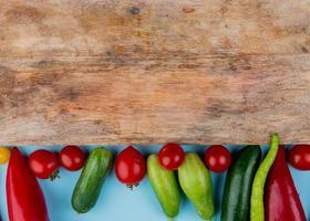 Verduras con una tabla de cortar sobre un fondo azul. foto