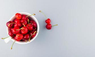top view of cup full of red cherries on left side and white background with copy space photo