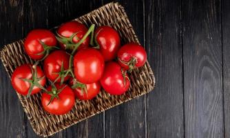 Top view of tomatoes in basket plate on wooden background with copy space