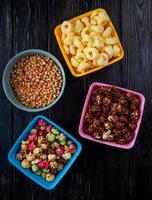 Vista superior de tazones con bolos y palomitas de chocolate, palomitas de maíz, cereales y semillas de maíz sobre fondo negro