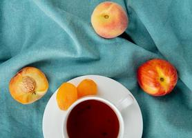 top view of cup of tea with raisins on teabag and peaches on blue cloth background photo