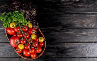 top view of vegetables as tomatoes coriander basil in basket on wooden background with copy space photo