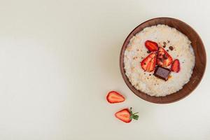top view of bowl of oatmeal with cottage cheese chocolate and strawberries on right side and white background with copy space