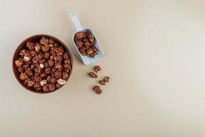top view of bowl and spoonful of chocolate popcorn on left side and white background with copy space