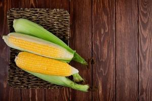 top view of basket plate with corns on left side and wooden background with copy space photo