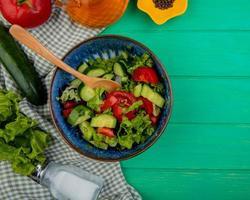 Vista superior de ensalada de verduras con tomate, lechuga, pepino, sal y pimienta negra sobre tela y fondo verde con espacio de copia